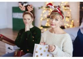 不高兴的女孩打开圣诞礼物的肖像_11755865