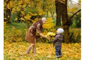 妈妈和儿子一起在秋天的公园散步和玩耍_11029957