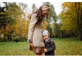 妈妈和儿子一起在秋天的公园散步和玩耍_11029985