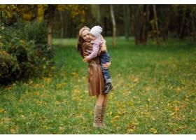 妈妈和儿子一起在秋天的公园散步和玩耍_11029998