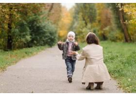 妈妈和儿子一起在秋天的公园散步和玩耍_11035210
