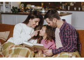 妈妈和爸爸带着女儿坐在沙发上看书_11766054