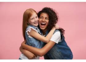 两个年轻开朗的漂亮女孩穿着家装站在粉色上_11863484