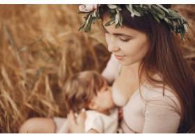 优雅的母亲带着可爱的小女儿在田野里_5557886