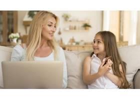 使用笔记本电脑和智能手机在家中看到母女俩_10604678