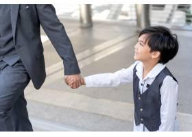 儿子牵着父亲的手在商业区城市_11872246