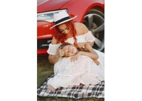 公园里美丽的一家人穿着白色连衣裙戴着帽_11160437