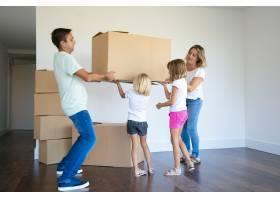 全神贯注的父母和两个女孩一起把箱子搬到新_10608121