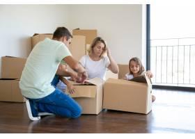 全神贯注的父母和孩子在新公寓里打开东西_10608118