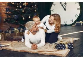 一家人带着年幼的儿子在圣诞树附近_11242905