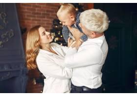 一家人带着年幼的儿子在圣诞树附近_11242930