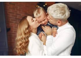 一家人带着年幼的儿子在圣诞树附近_11243356