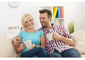 一对漂亮的情侣坐在沙发上喝着咖啡放松_10675028