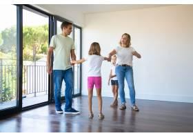 一对父母和两个孩子享受着他们的新家站在_10586211