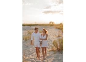 一对相爱的情侣穿着白衣走在海滩上全长_10688262