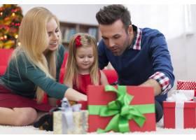 不耐烦的小女孩和父母一起打开圣诞礼物_10677104