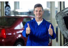 站在修理厂的机械师竖起大拇指_1005292