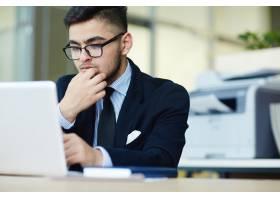 经理在办公室使用笔记本电脑工作_5400237