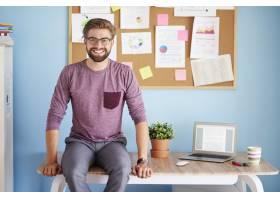 快乐的男人在办公桌上机智地坐着_13134053