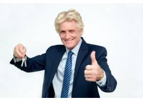 快乐的资深商人展示钥匙和竖起大拇指_1022687
