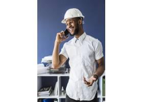 微笑的非洲建筑师在办公室用手机交谈_2572641
