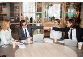 友善的男同事或伴侣在团队会议上拳头相撞_3953834