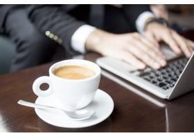 咖啡馆里用笔记本电脑工作的男子的裁剪视图_1304575