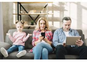 愤怒的女儿和她的父母坐在沙发上使用数字平_3808497