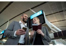 商务人士手持登机牌使用手机_10747859