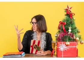 困惑的女商人戴着眼镜拿着她的礼物坐在_13406817