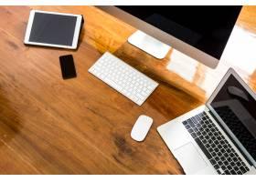 在一张木桌上放着笔记本电脑电脑和手机_992533