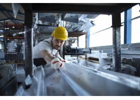 在仓库工作的工厂工人搬运生产用的金属材料_11035572