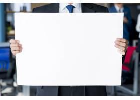 一位商人手持空白白色标语牌的特写_3115111