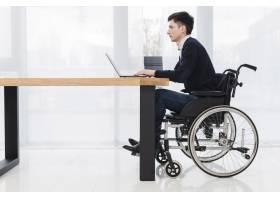 一位年轻商人坐在轮椅上在新办公室里使用_4409218