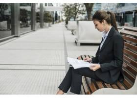 一位年轻女商人坐在长椅上阅读文件的侧视_3681689