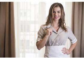 一位年轻的女服务员手持衣领站在酒店房间的_3688505