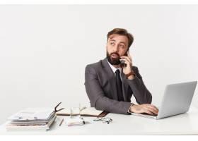 一位年轻迷人的留着胡须的商人在电话中讨论_10786841