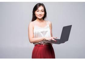 一位快乐的亚洲妇女在隔绝在白墙上的笔记本_8472566