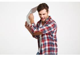 一位怒气冲冲的男子扔掉他的笔记本电脑的肖_7437940