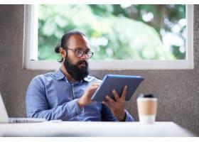 一位戴眼镜的留着胡子的印度男子坐在办公室_5839218