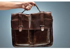 一名男子拿着一个棕色皮革旅行包_8923762