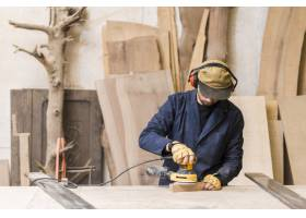 一名男木匠在木头上使用电动砂光机的特写_3564588