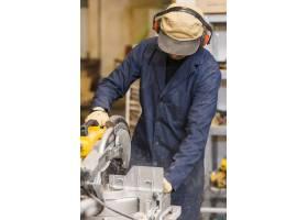 一名男木匠在木工车间使用电动工具工作_3564565