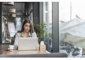 一名自由职业女性在咖啡厅用笔记本电脑工作_3621123