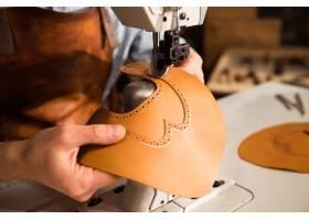 一名鞋匠在皮革纺织品上工作的特写镜头_7573547