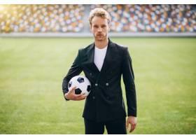 身着西装的英俊足球运动员在体育场_5507444