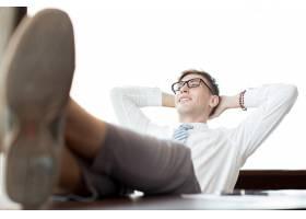 轻松的商务人士坐着双腿放在桌子上_1196423