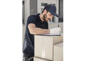送货员在堆叠的纸箱上的剪贴板上写字_2657237