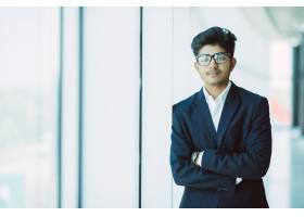 站在现代办公室的印度年轻商人_9076272