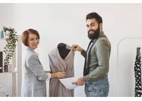 笑容可掬的时装设计师在工作室里穿着礼服_12364416